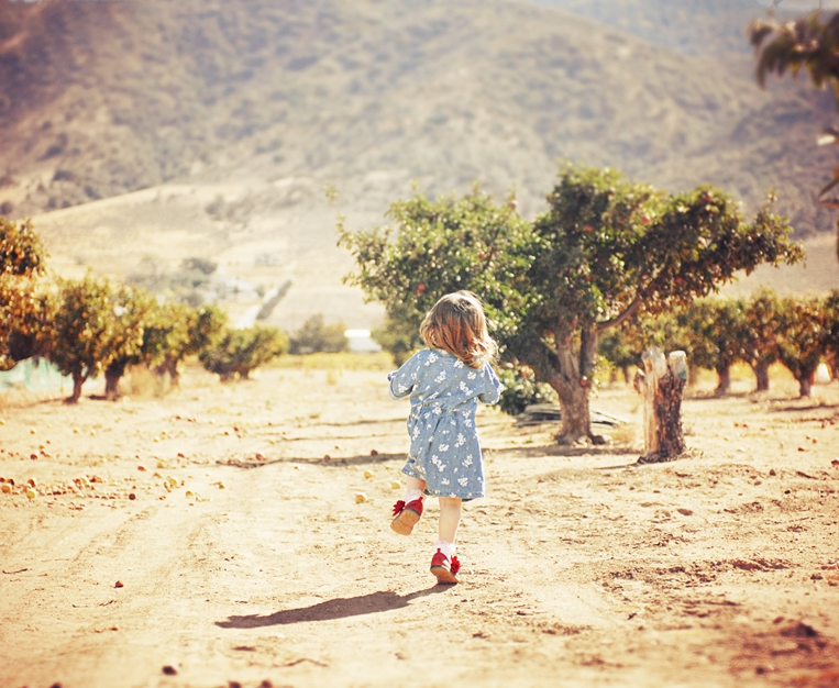 girl-blue-dress-red-shoes-running-apple-orchard